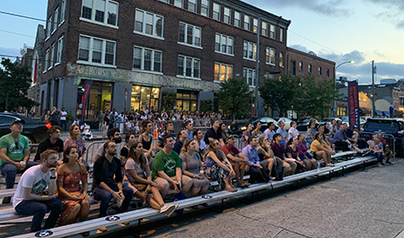 Visitors watching the films on bleachers outside along Fairmount Avenue