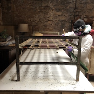 A conservator cleans a bed frame